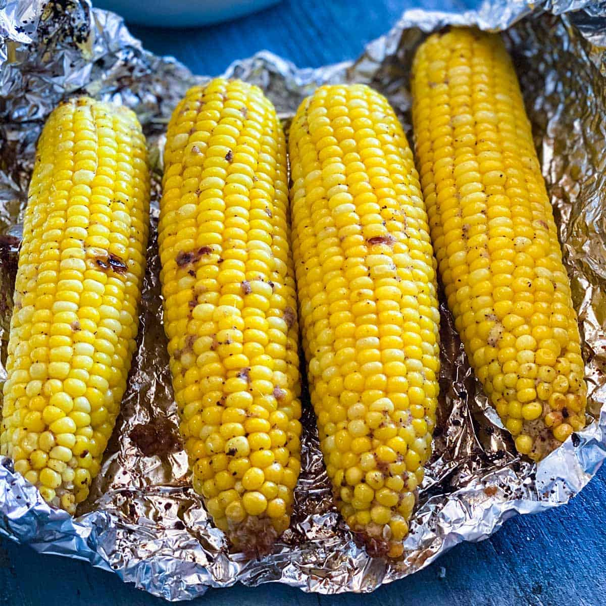 Close up of four grilled corn on the cob in a foil pack for How to Grill Corn on the Cob in Foil