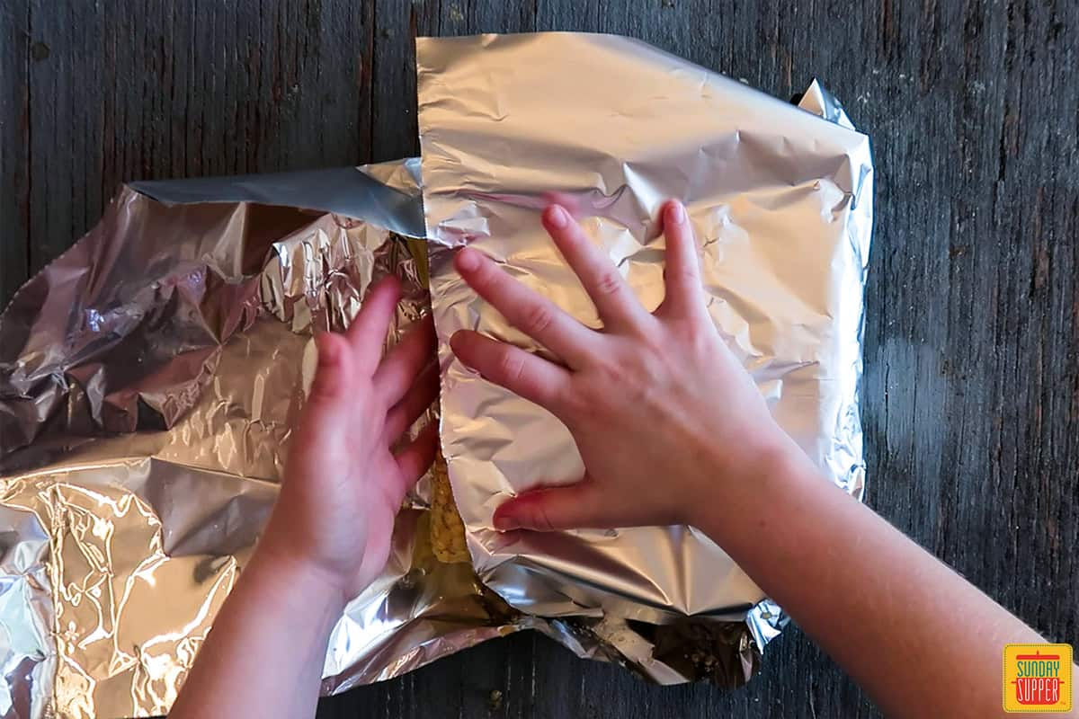Folding one half of the foil over the four corn cobs