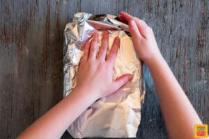 Folding the second half of foil over the corn cobs