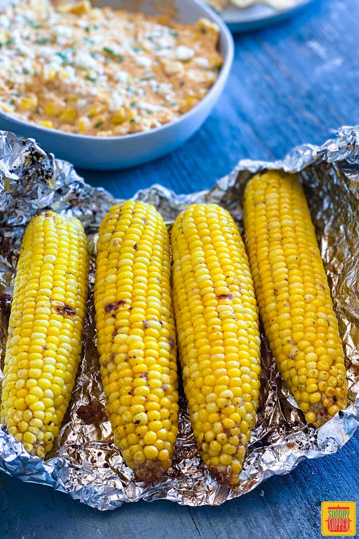 Close up of four grilled corn cobs on a piece of foil