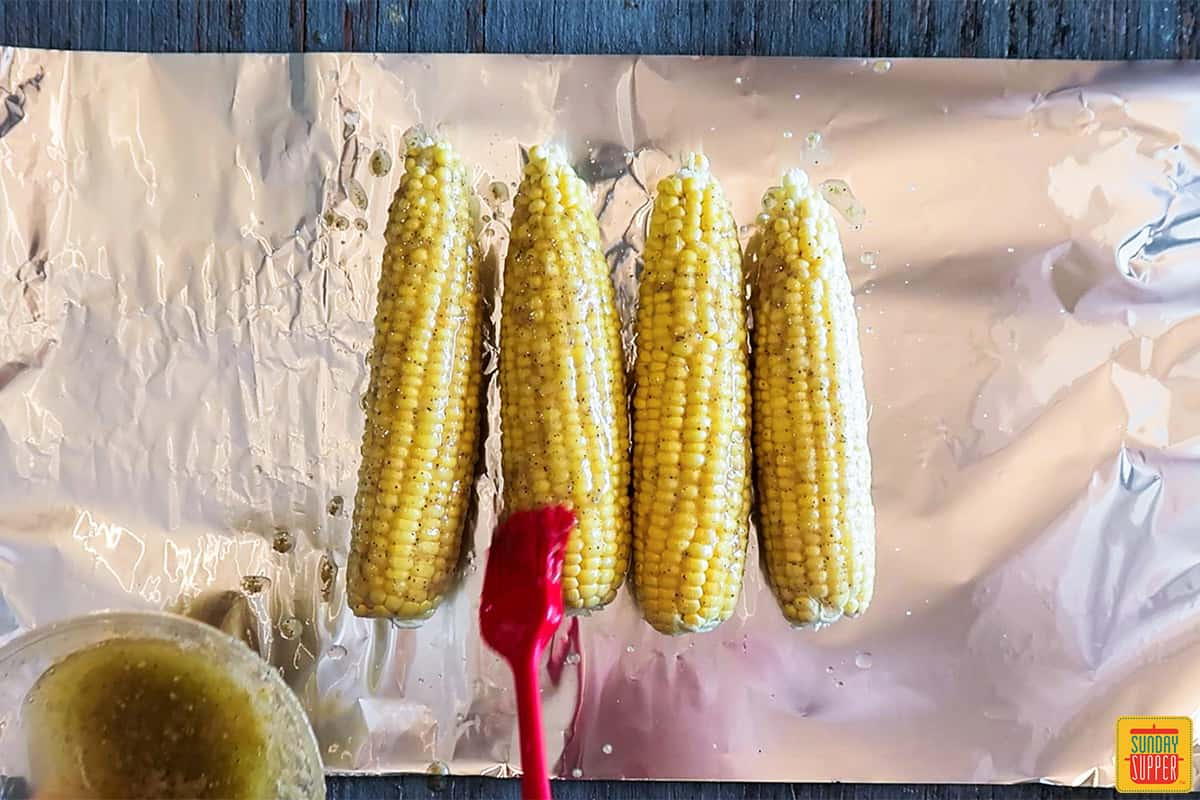 Brushing garlic butter sauce onto four corn cobs over a sheet of foil
