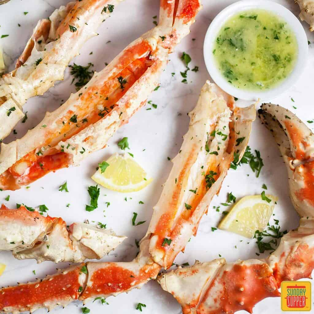 Grilled crab legs on a white surface with lemon wedges, fresh herbs, and a white cup of garlic butter sauce