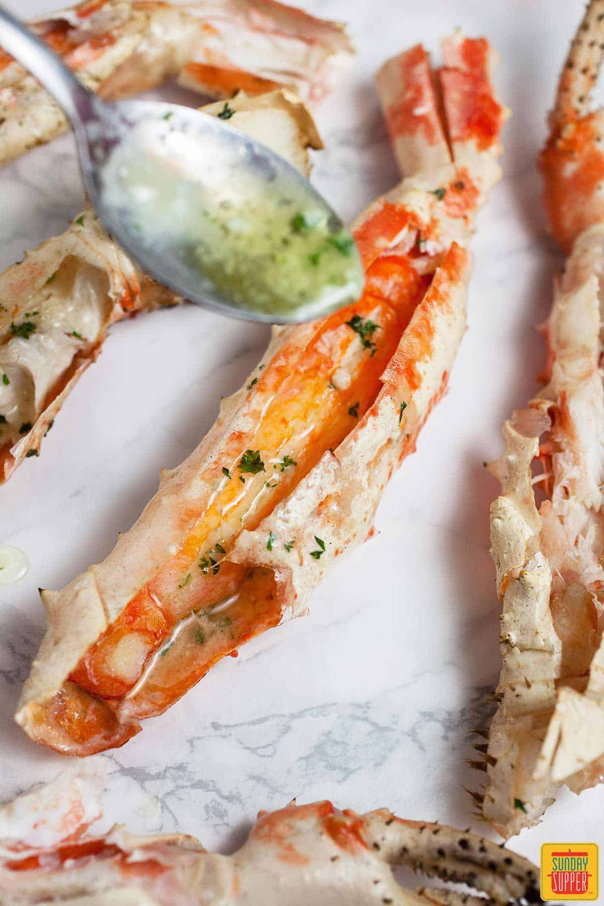 Pouring garlic butter sauce onto grilled king crab legs