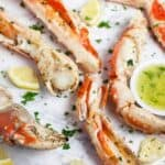 Grilled crab legs on a white surface with fresh herbs and a side of garlic butter in a little bowl