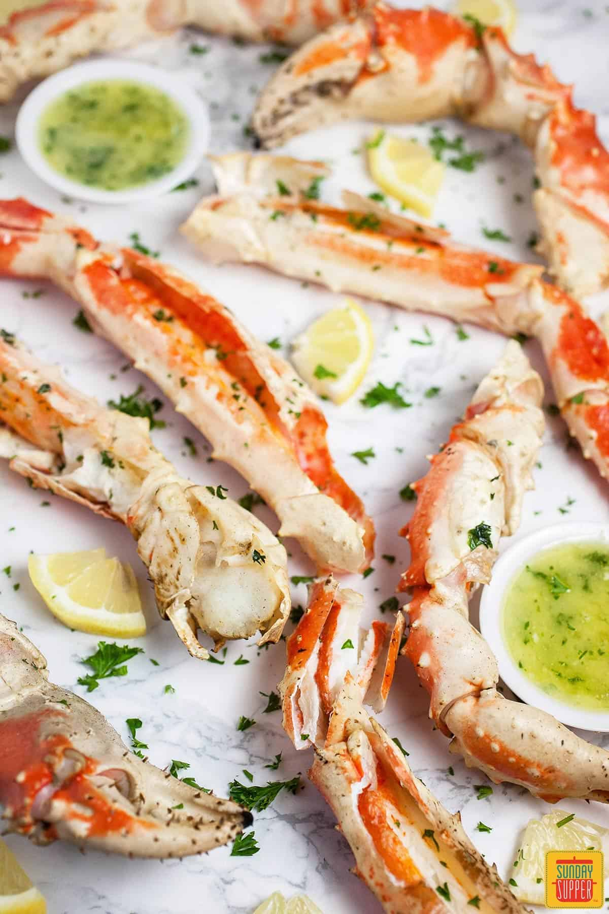 Grilled crab legs on a white surface with two cups of garlic butter sauce and fresh herbs sprinkled on