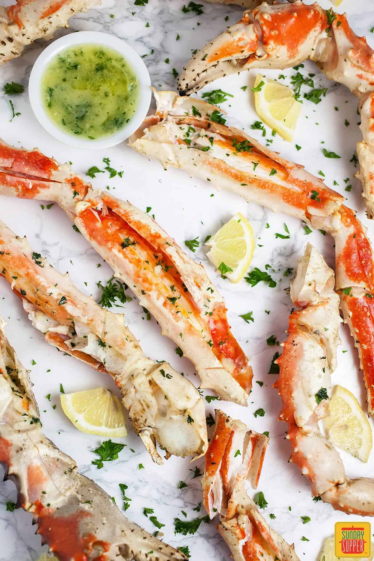 Grilled crab legs on a white surface with a cup of garlic butter sauce and fresh herbs sprinkled on top