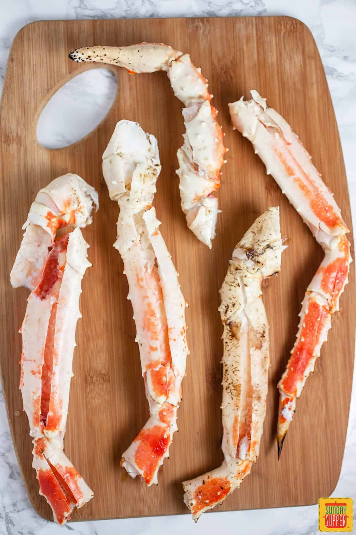 King crab legs on a wooden cutting board