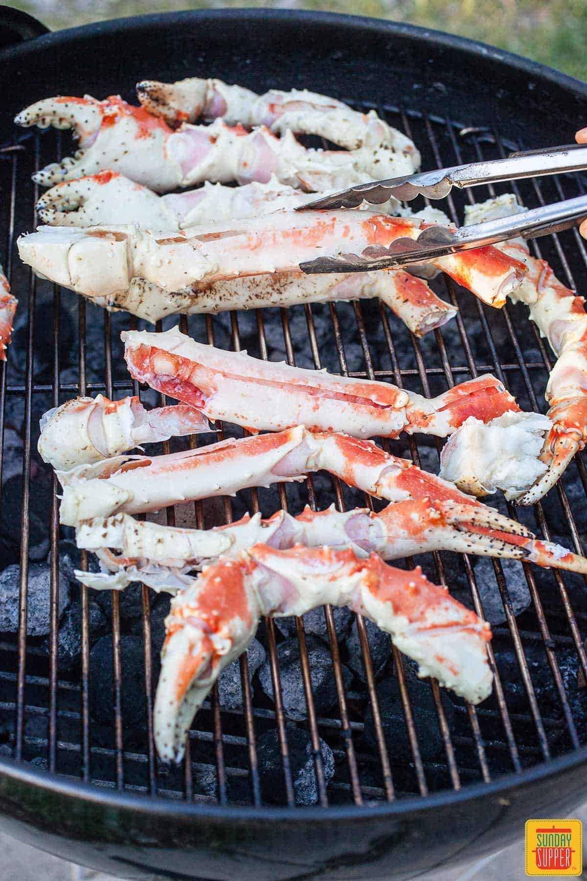 Lifting crab legs off the grill over with some tongs