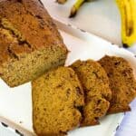 Three slices of Instant Pot Banana Bread next to a loaf of banana bread on a white platter