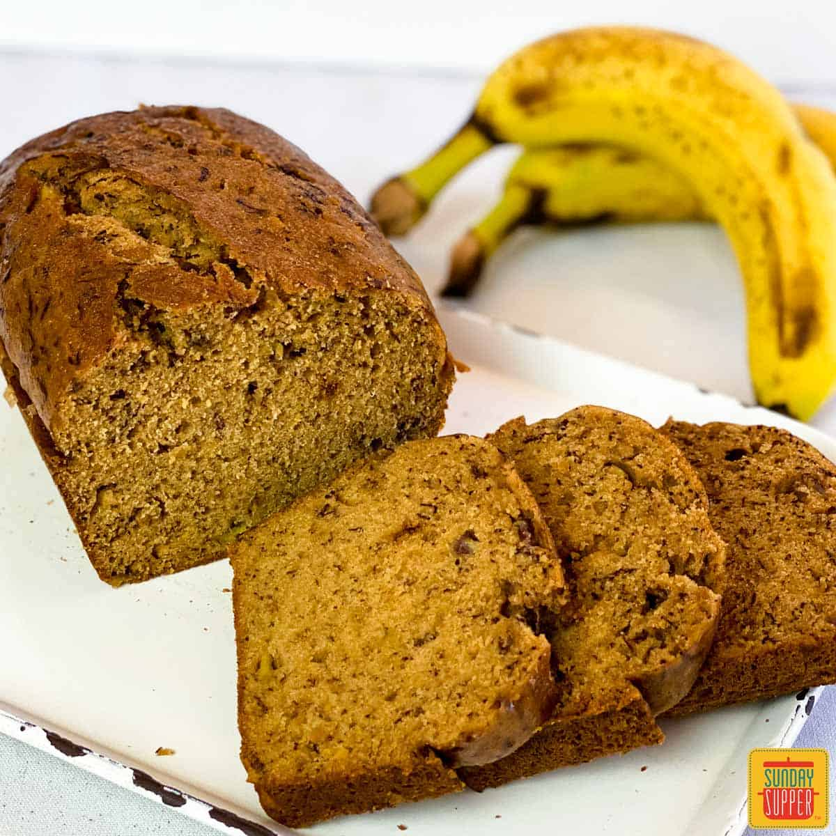 Three slices of banana bread next to a loaf of Instant Pot Banana Bread on a white platter with two bananas in the background