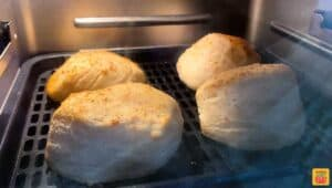 Four biscuits in the air fryer on a rack