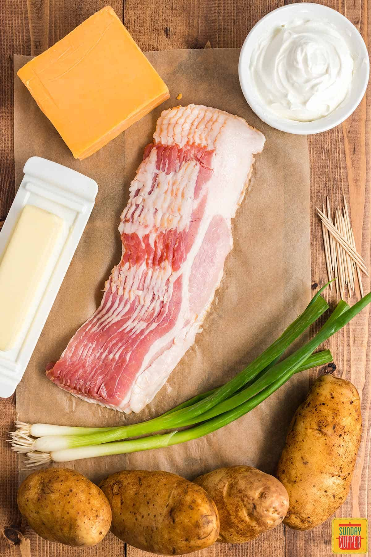 Ingredients laid out on a wooden surface to make potatoes wrapped in bacon: a block of cheddar cheese, a stick of butter, several slices of uncooked bacon, fresh green onions, russet potatoes, and a white bowl of sour cream, plus a stack of toothpicks