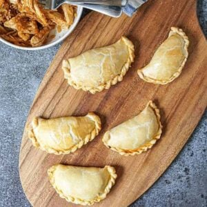 baked empanadas on a wood board