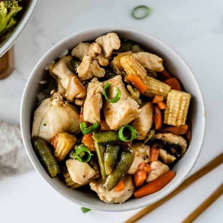 Easy 5-ingredient chicken stir fry in a white bowl with chopsticks to the side