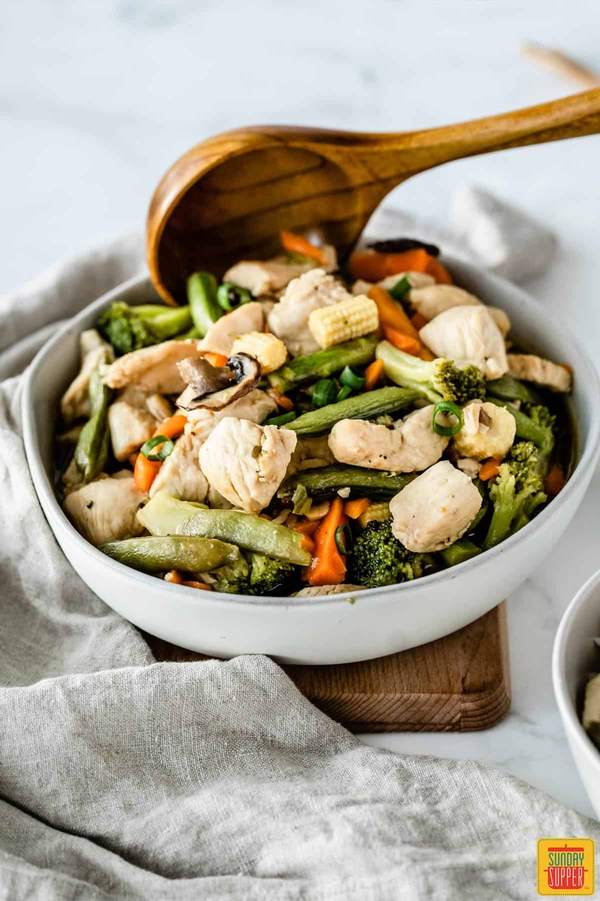 Using a wooden spoon to dish out chicken stir-fry from a white bowl
