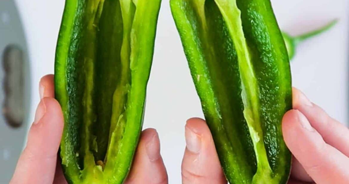 Holding two halves of a jalapeno pepper with the seeds removed for how to cut a jalapeno