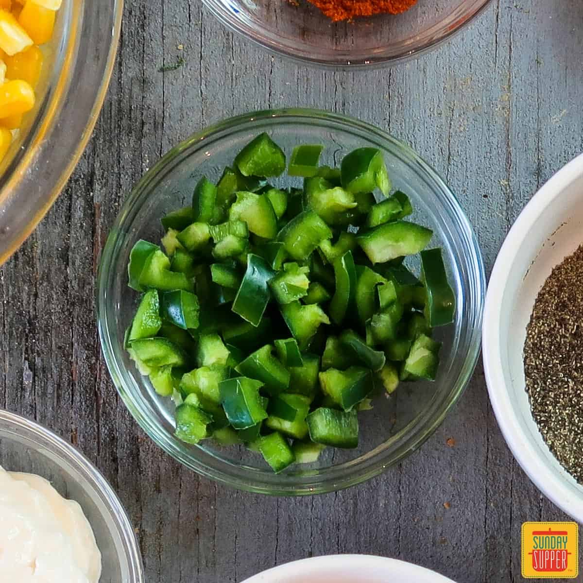 A glass bowl of diced jalapeno to show you how to cut a jalapeno