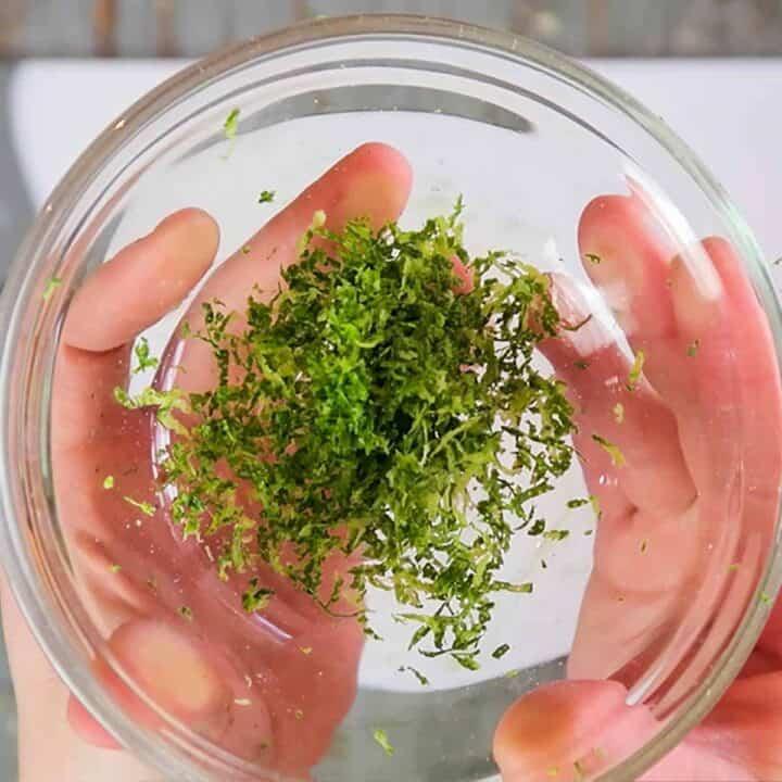 Holding a clear glass bowl with lime zest in both hands