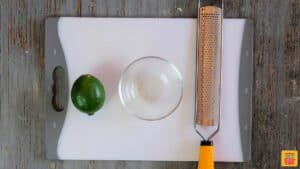 The tools you need for how to zest a lime: a grater, bowl, and lime, on a cutting board