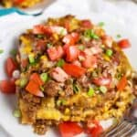 Mexican lasagna recipe served on a white plate with tomatoes and green onions