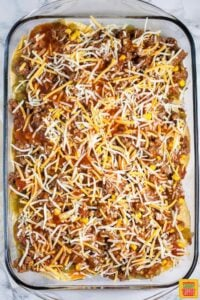Adding the final layer to Mexican lasagna recipe with tortillas