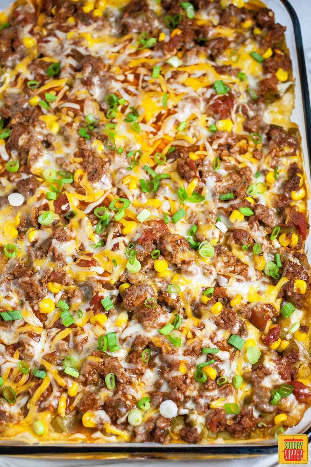Mexican lasagna with corn tortillas in the casserole dish after baking