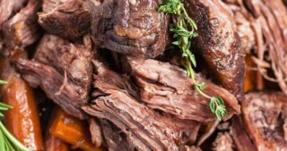 Close up of Dutch Oven pot roast meat with herbs and carrots