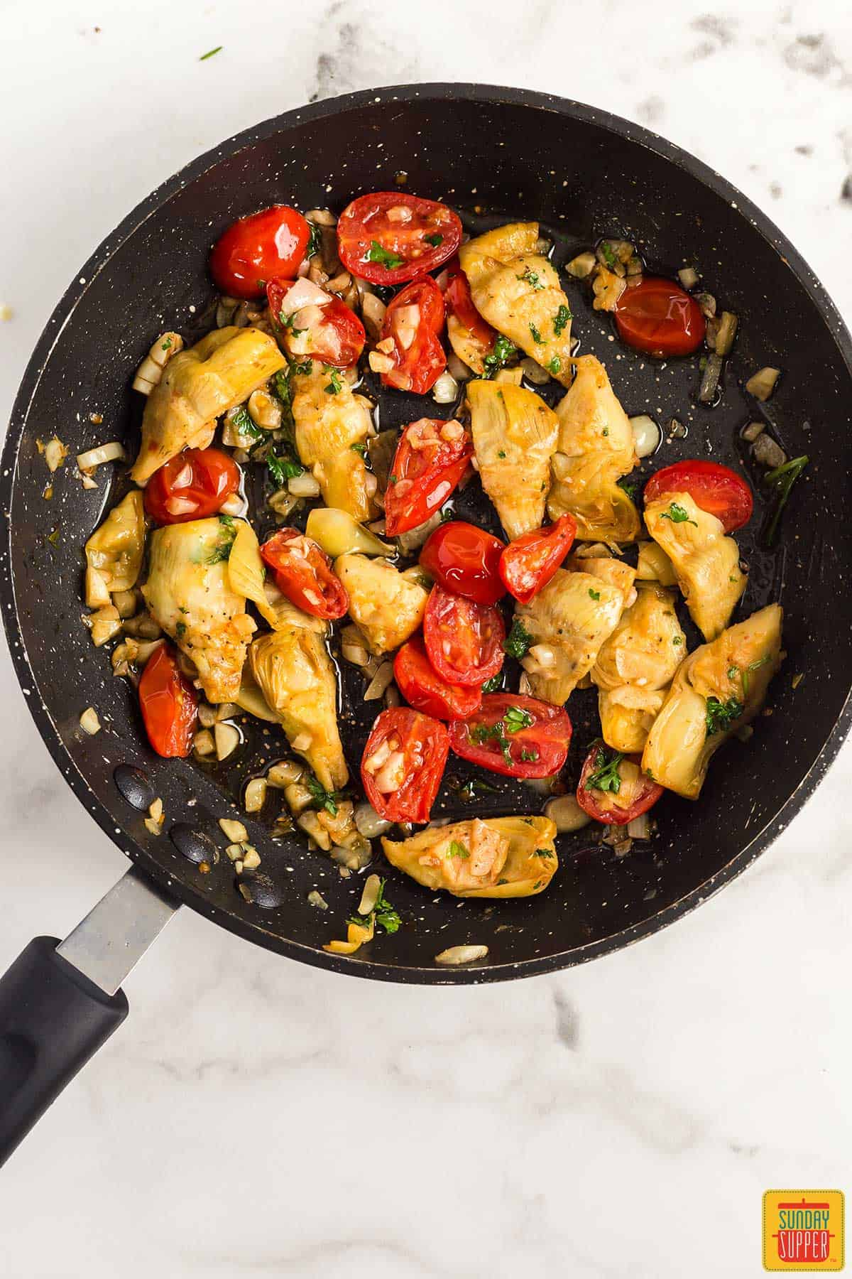 Garlic, artichokes, and tomatoes cooking in a skillet