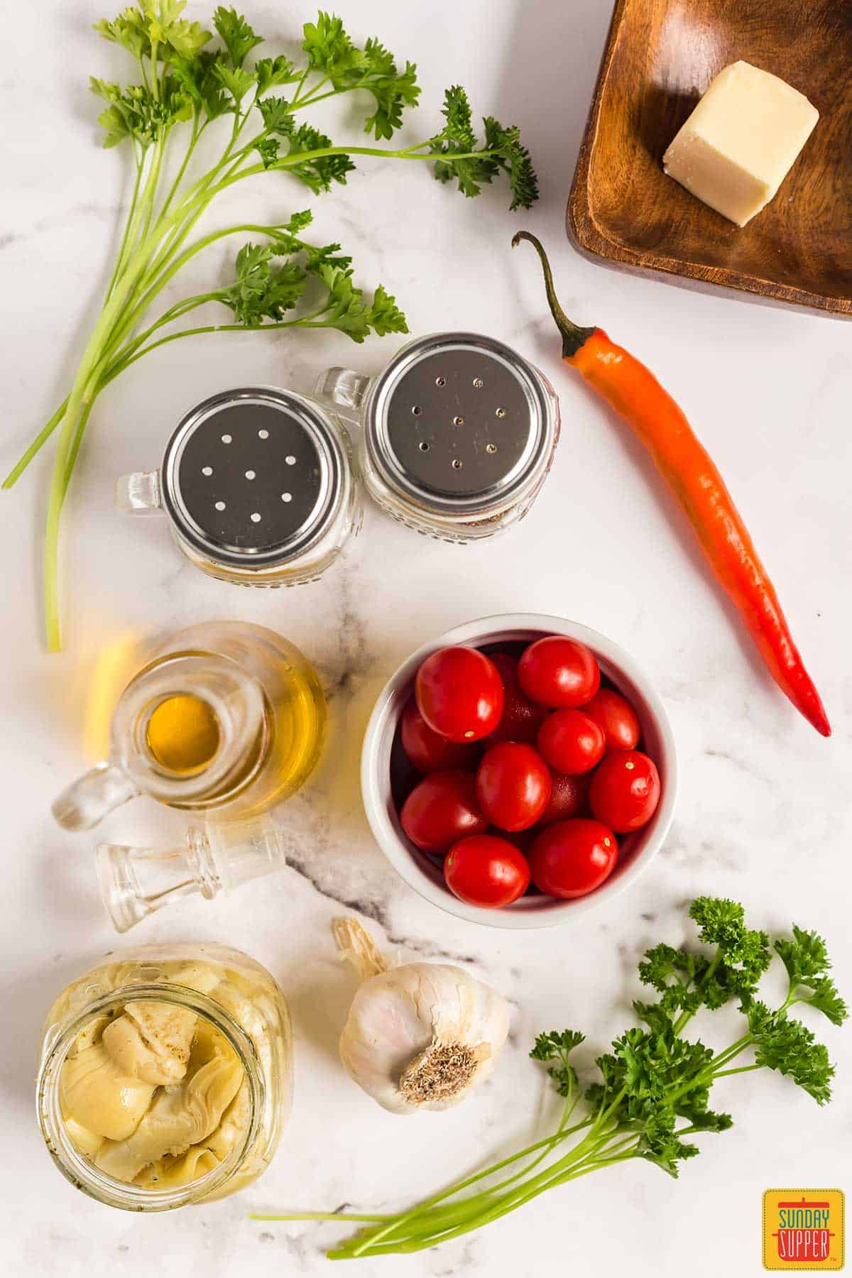 Ingredients to make the recipe on a white surface: cherry tomatoes, parsley, garlic, artichoke hearts, olive oil, a red chili pepper, salt and pepper shakers, and butter