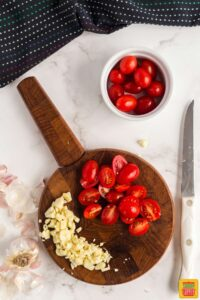 Halved cherry tomatoes and chopped garlic on a round wooden board