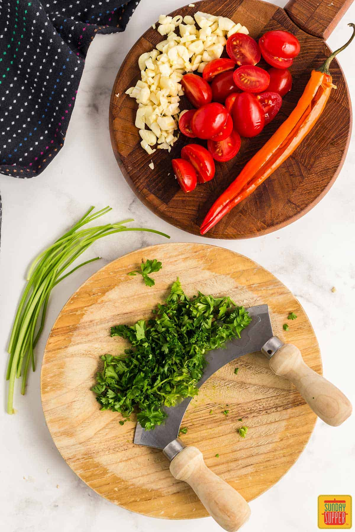 Chopped parsley next to sliced red chili pepper, minced garlic, and halved cherry tomatoes on two separate wooden boards