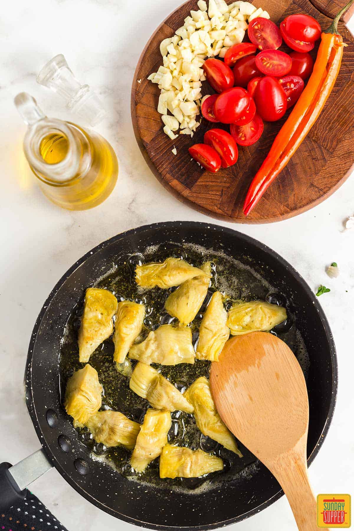Cooking artichoke hearts in a skillet with olive oil