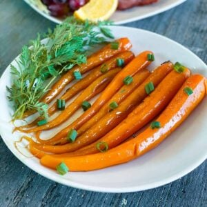 Candied carrots on a white plate with fresh herbs and green onions