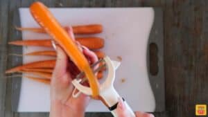 Peeling a carrot over a white cutting board