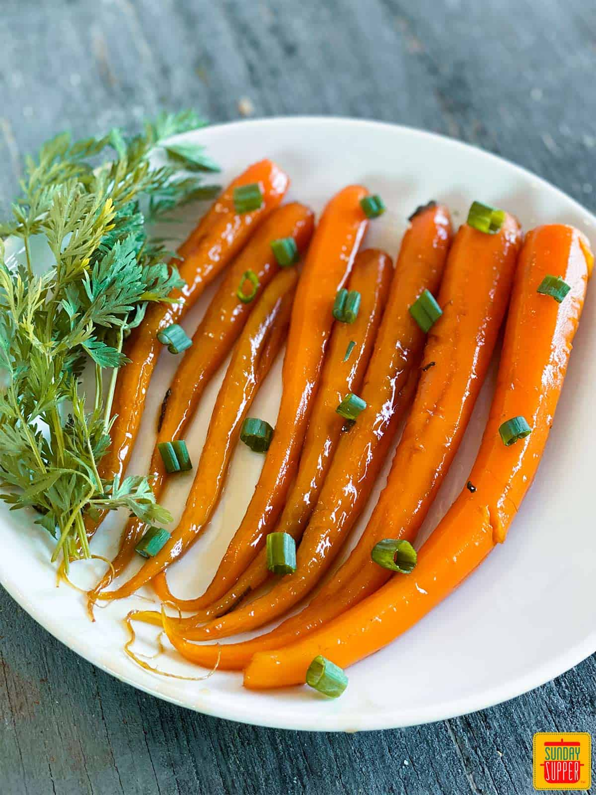 Candied carrots close up on a white plate