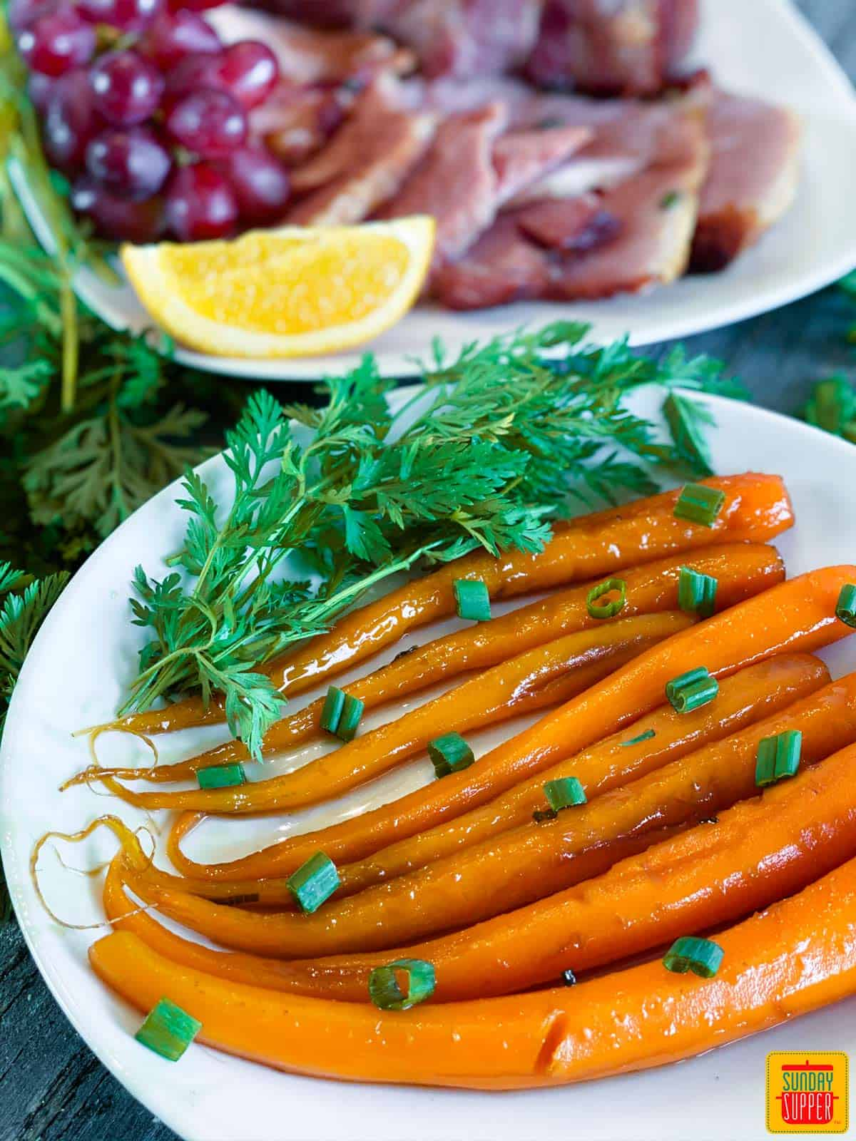 Candied carrots close up on a white plate in front of ham slices and citrus on a platter