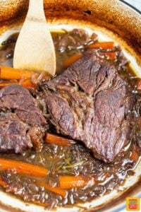 Cooked pot roast in the dutch oven with a wooden spoon