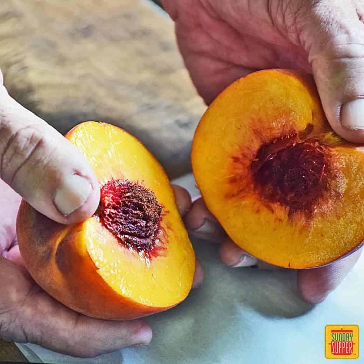 Holding a peach half in each hand