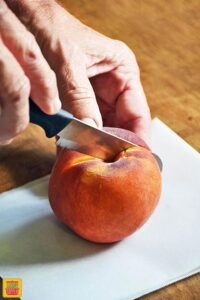 Holding a peach to cut it through the middle with a knife