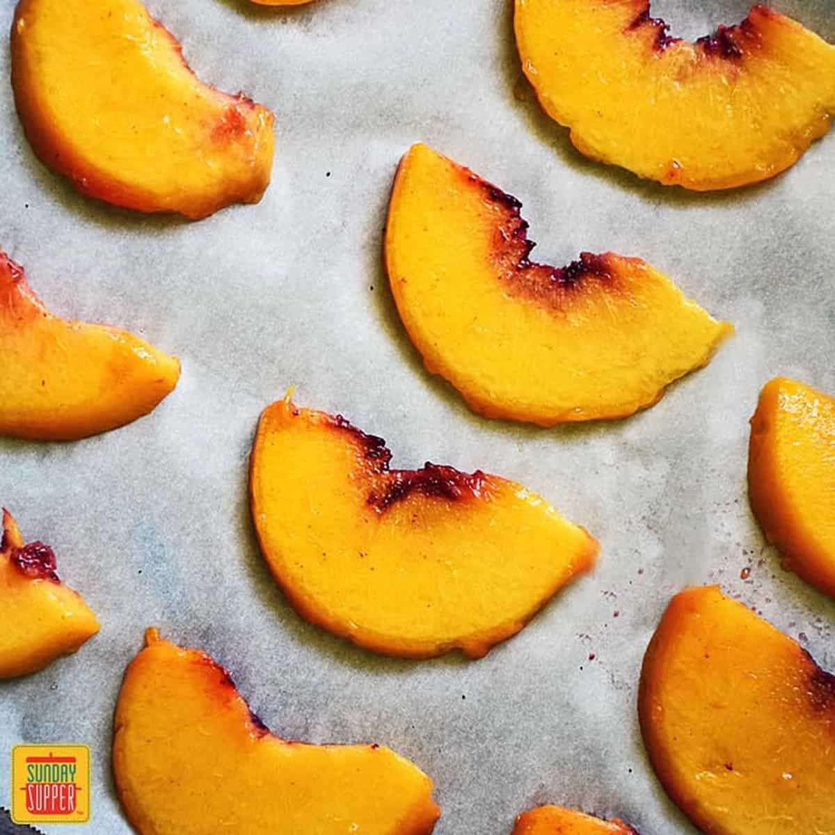 Peeled peach slices on parchment paper in rows