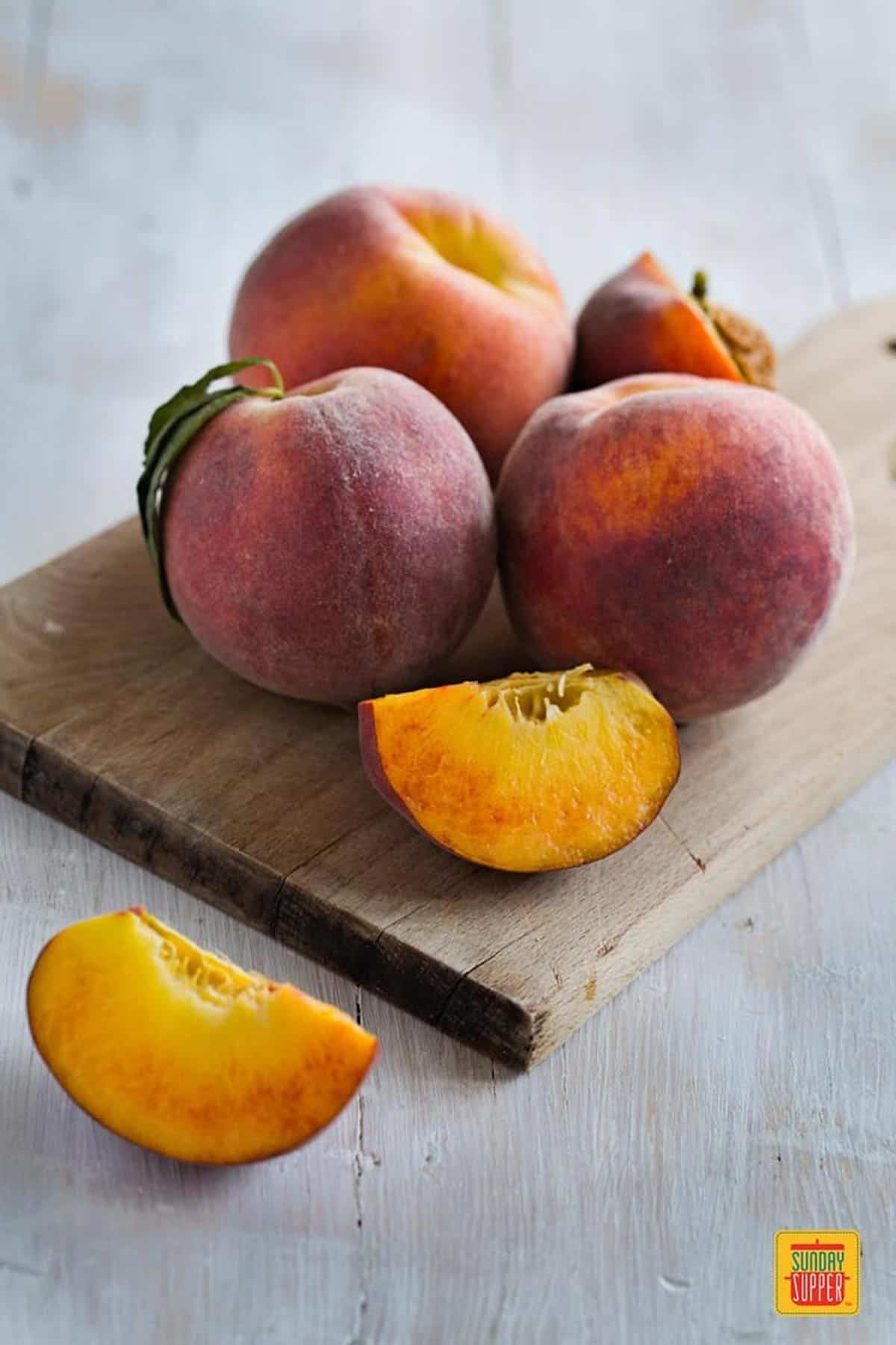 Two quarters of a peach next to three whole peaches and half a peach on a wooden board