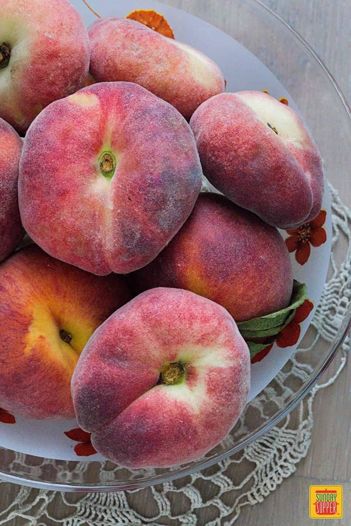 Peaches stacked on a floral plate over a glass platter