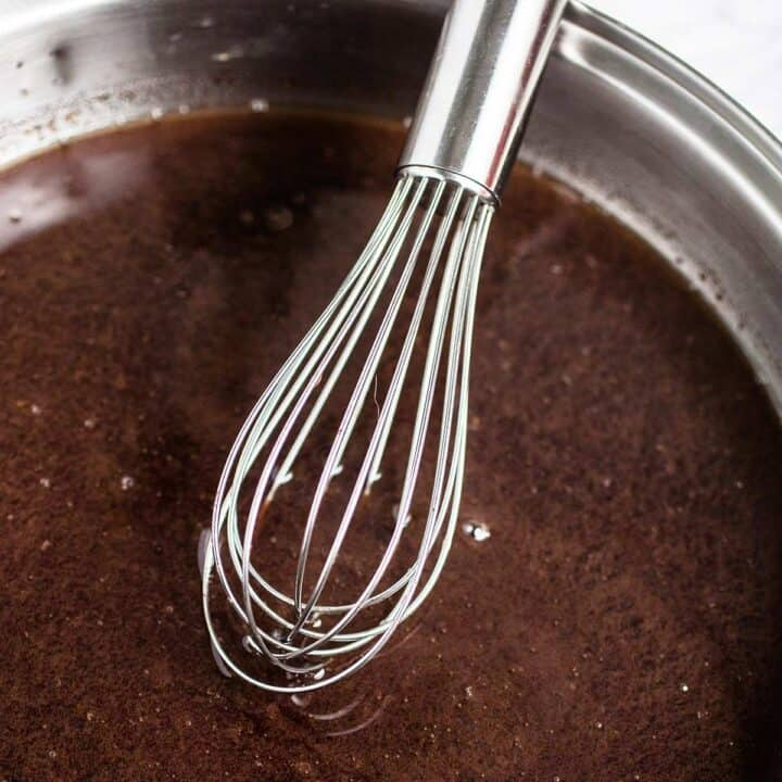 A whisk hovering over a metal bowl of au jus