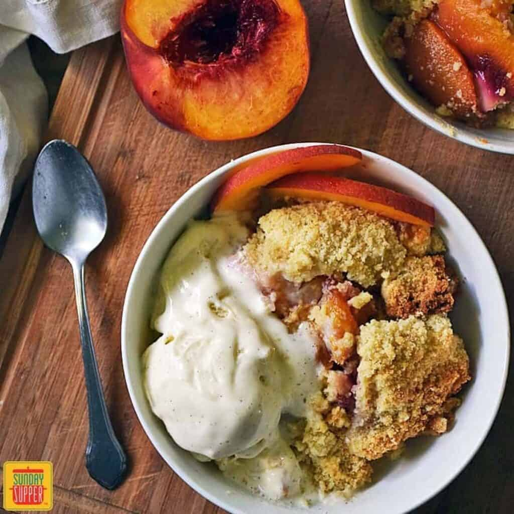A white bowl of peach cobbler with cake mix with ice cream on top next to a spoon and half a peach