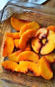 Peeled and sliced peaches in a glass baking dish