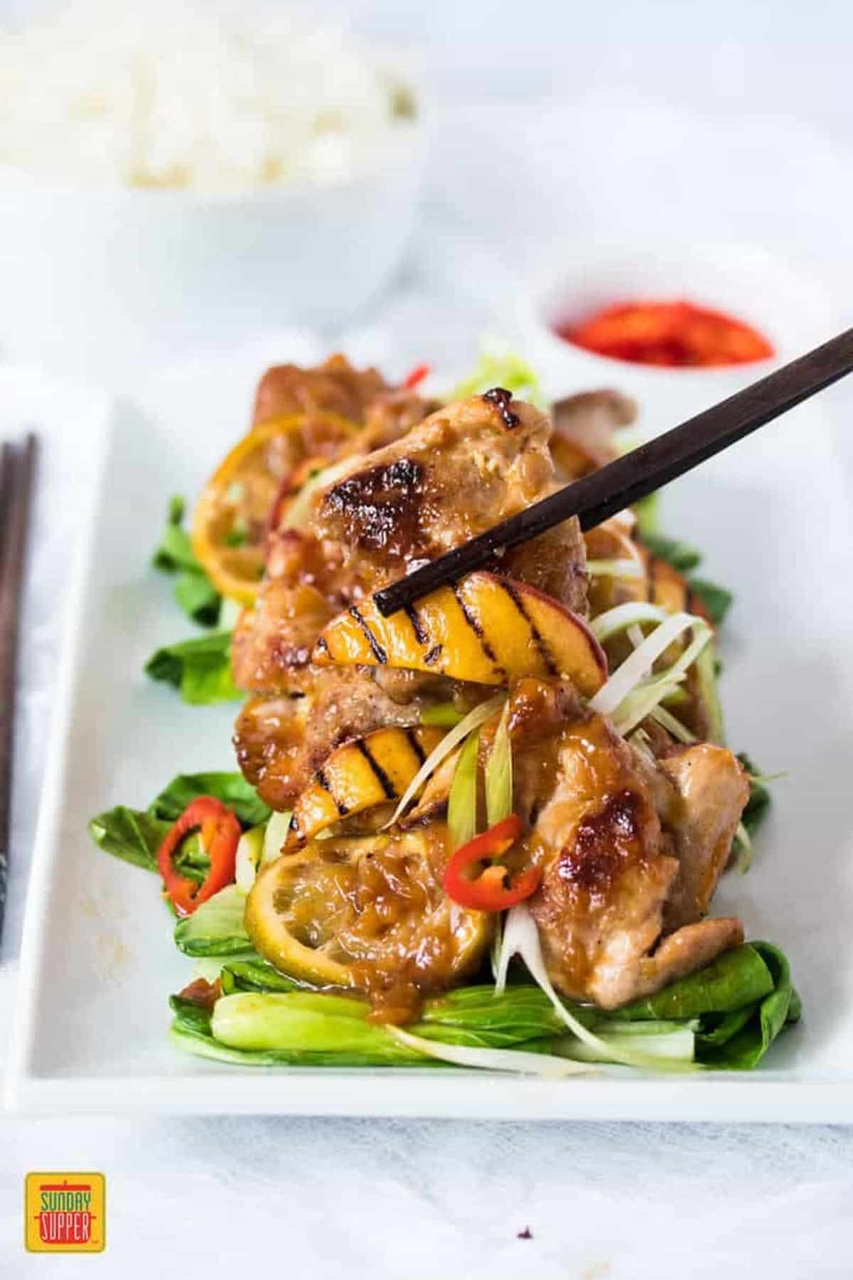 Lifting a piece of peach glaze chicken with a grilled peach slice using chopsticks
