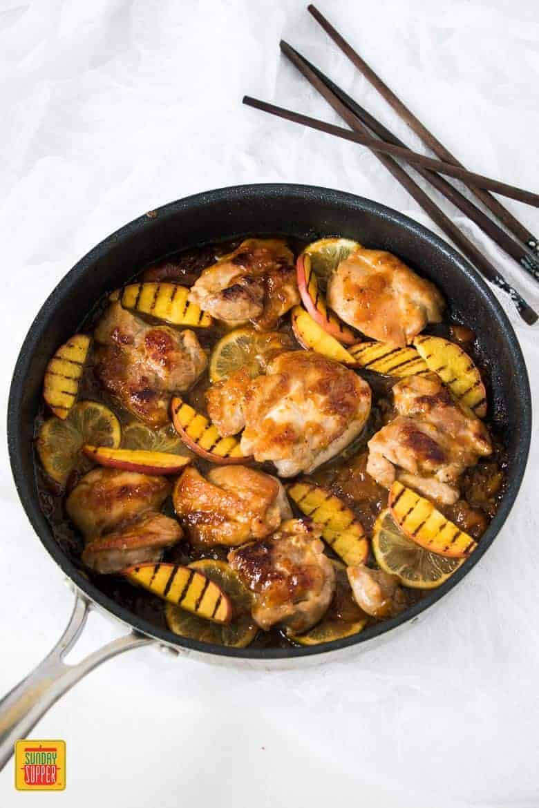 Peach glaze chicken cooking in a skillet with peaches and citrus next to chopsticks
