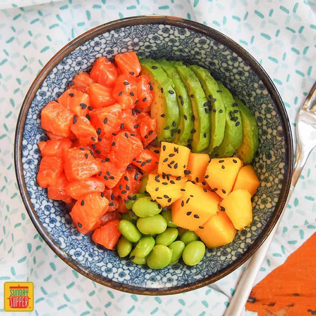 Salmon poke bowl with sesame seeds, avocado, mango, and edamame in a blue and white bowl