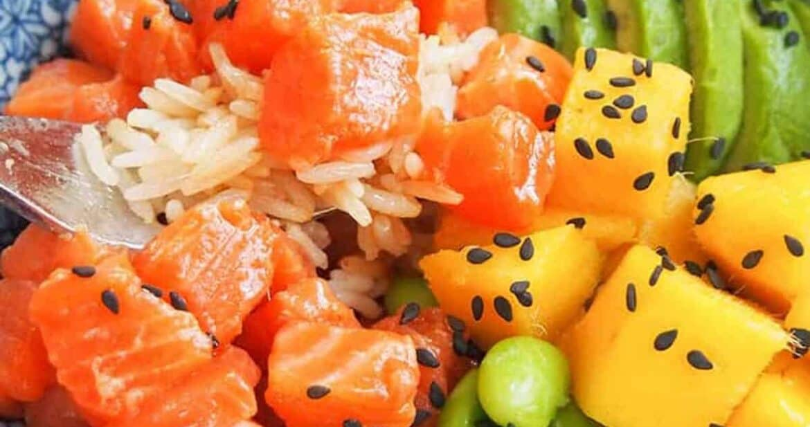 Close up of a forkful of salmon in a salmon poke bowl