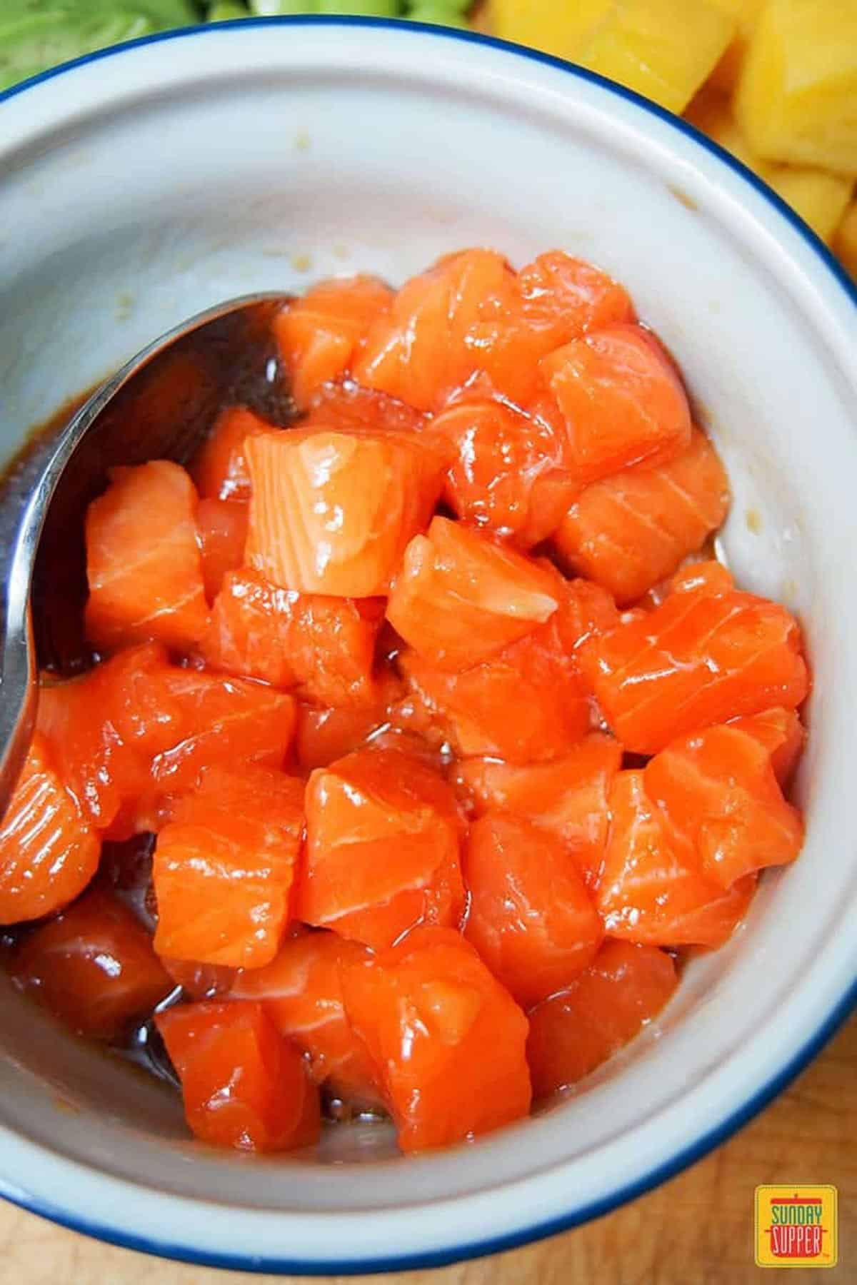 Salmon marinating in poke bowl sauce with a spoon to the side
